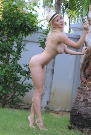 Isabella B in a short dress and hat getting naked under a palmtree